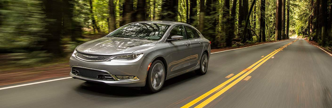 2017 Chrysler 200 driving down a road in the woods