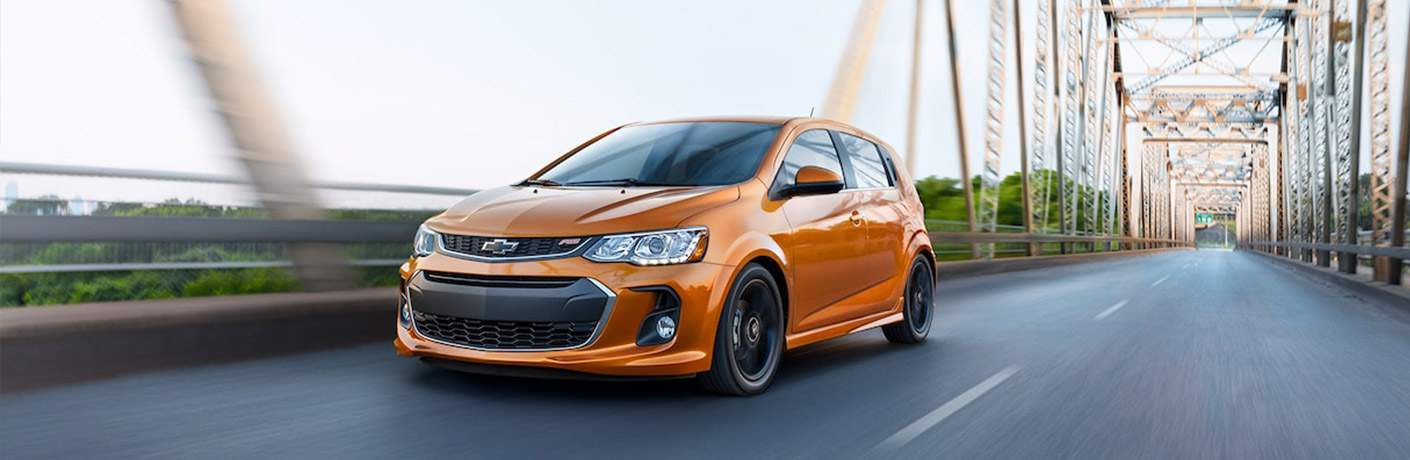 Orange Chevy Sonic driving over a suspension bridge