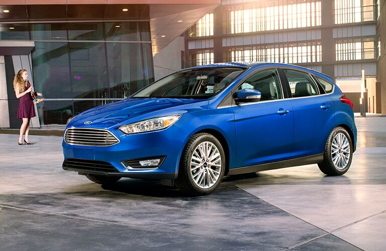 2018 Ford Focus in blue parked in front of a modern glass and concrete building