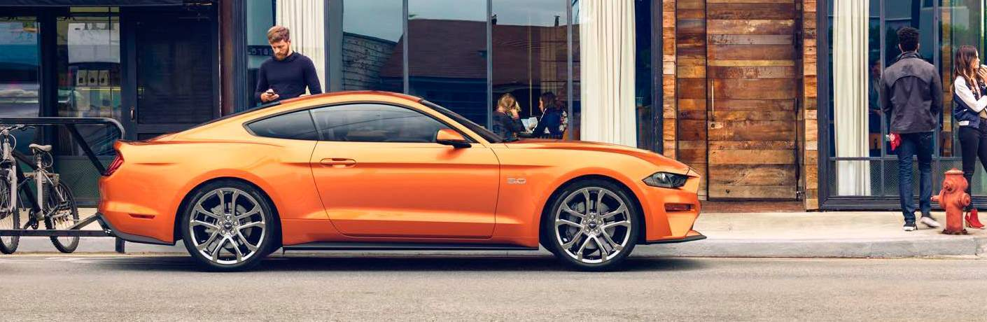 2018 Ford Mustang in bright orange parked in front of a small cafe