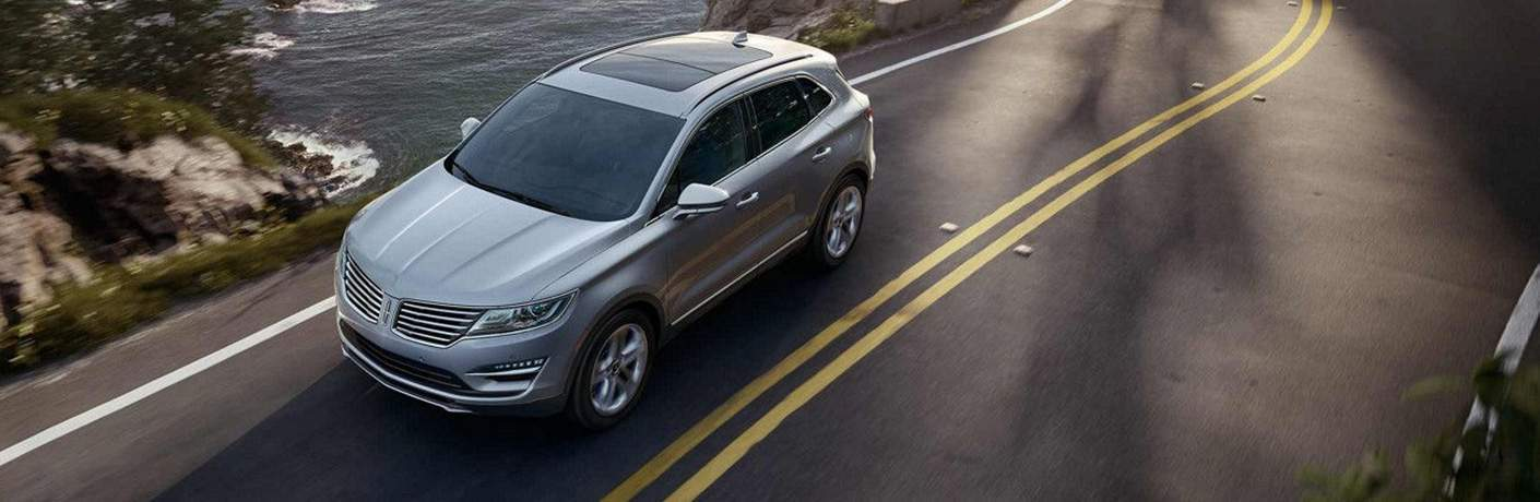 Overhead shot of the 2018 Lincoln MKC in grey driving down a country road