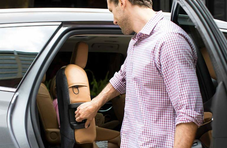 Man pulling back the second-row seat in the 2018 Buick Enclave
