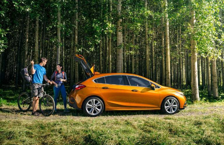 2018 Chevy Cruze in orange parked in the woods