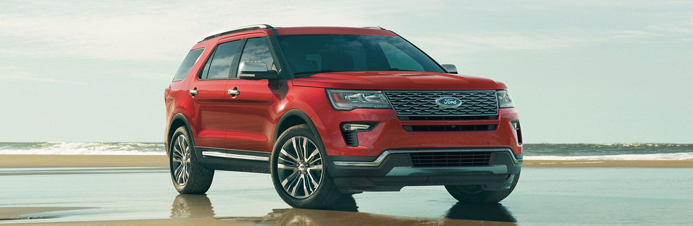 2019 Ford Explorer in red parked on a sandy beach