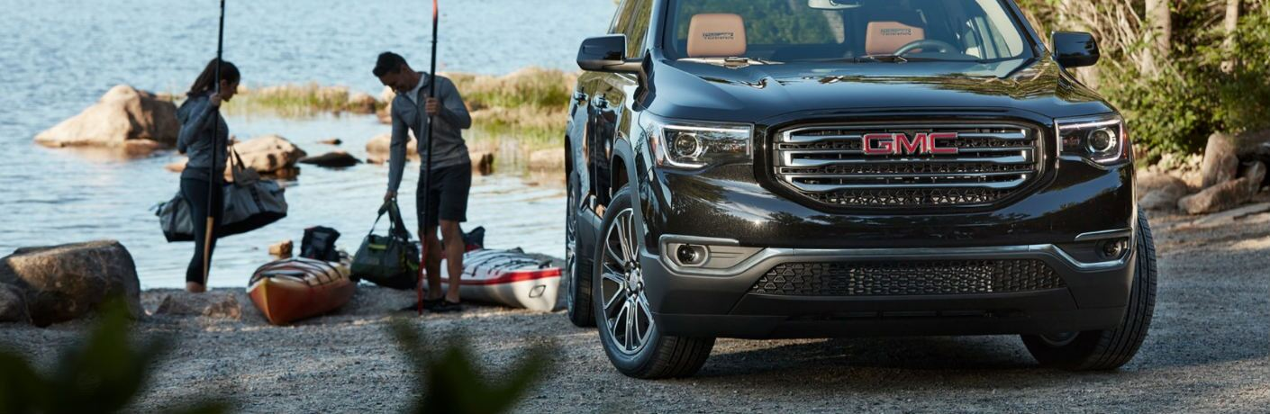 2019 GMC Acadia parked near a river and two people kayaking