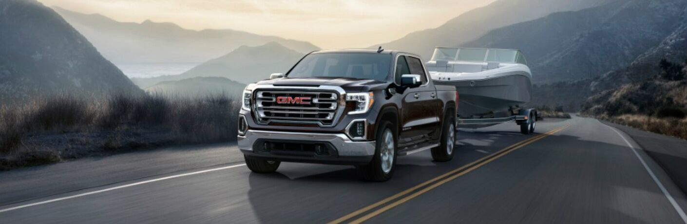 2019 GMC Sierra driving in the mountains while hauling a speed boat