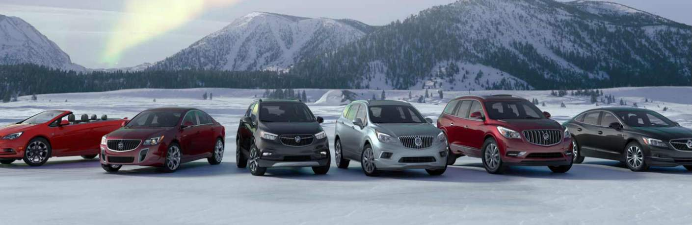 Buick lineup of vehicles parked in the snow at the base of a mountain