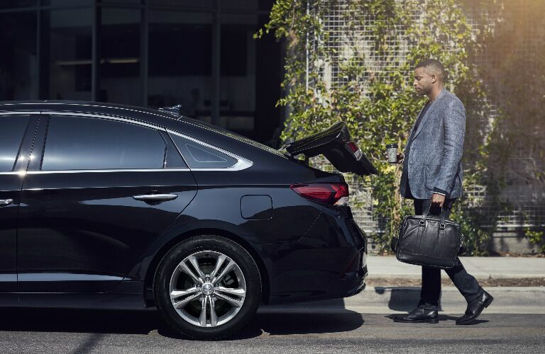 Man putting luggage into the trunk of the 2019 Hyundai Sonata