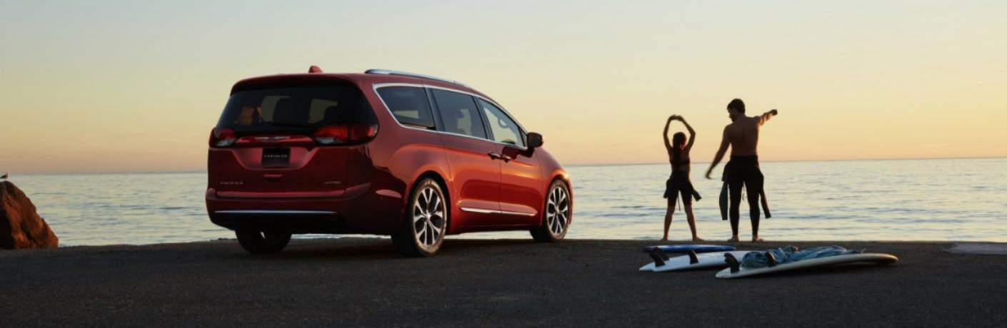Father and daughter surfing at the beach with the 2018 Chrysler Pacifica in the background