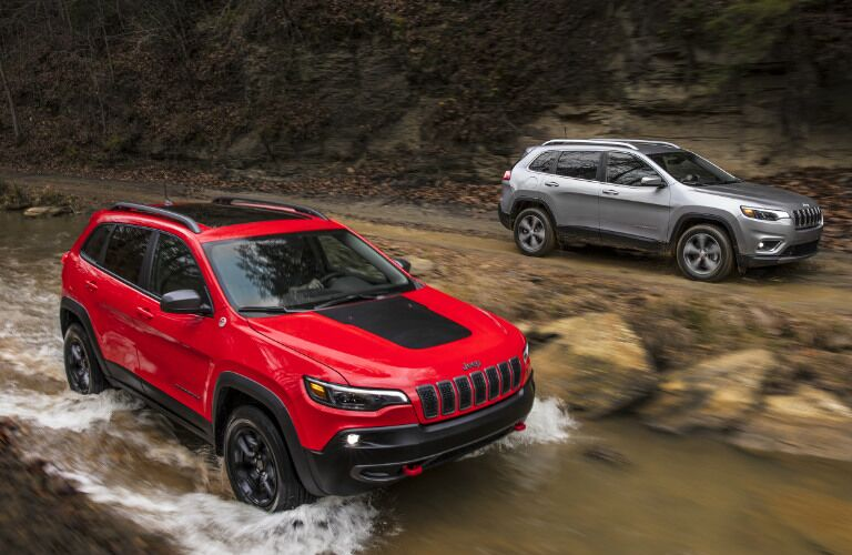 Two 2019 Jeep Cherokee models driving in and near a wooded stream