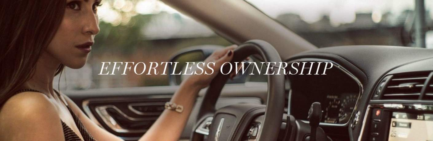 woman driving a Lincoln with text that says effortless ownership