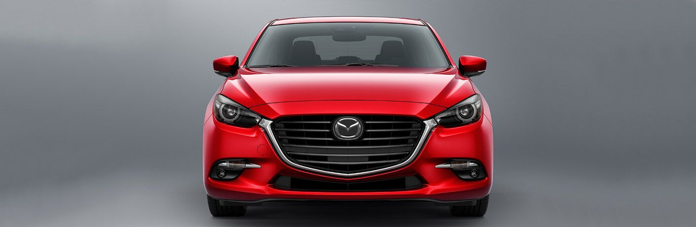 Front grille and headlights of red 2018 Mazda3 on silver background