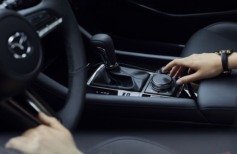Hand on steering wheel and hand on control knob in 2019 Mazda3
