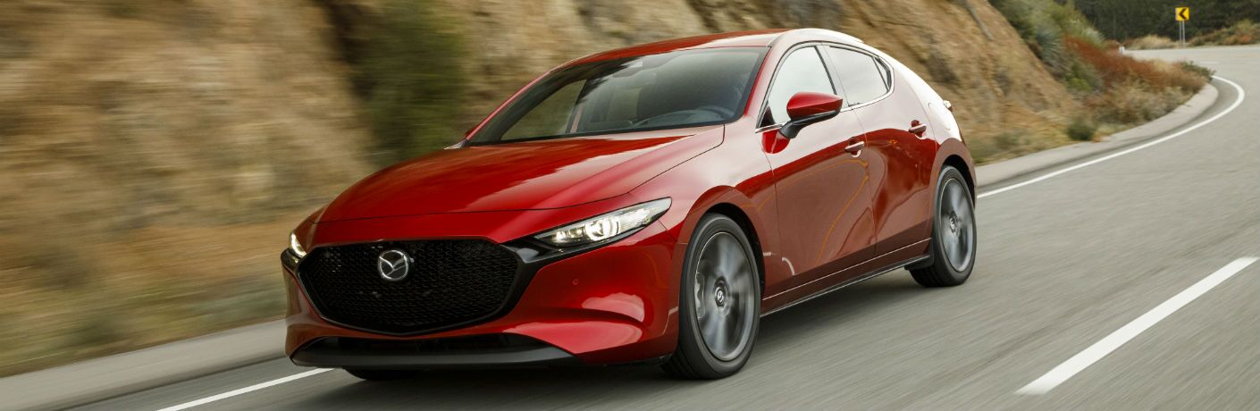 A front left quarter photo of the 2019 Mazda3 Hatchback on the road.