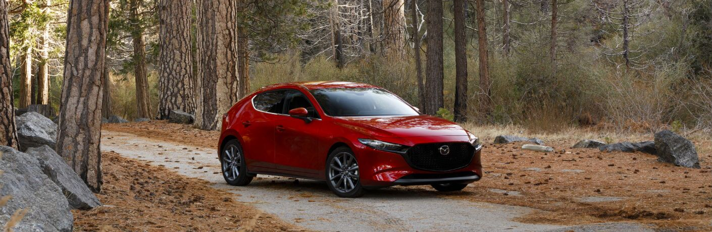 A right front quarter photo of the 2019 Mazda3 Hatchback parked in the woods.