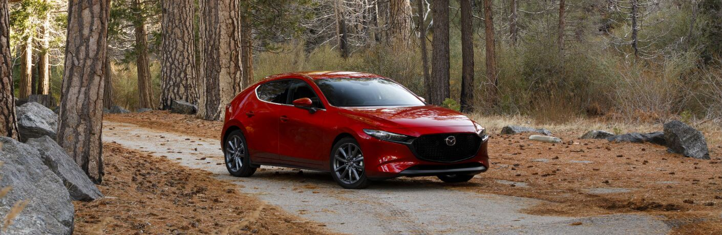 A front right quarter photo of the 2019 Mazda3 Hatchback in the woods.