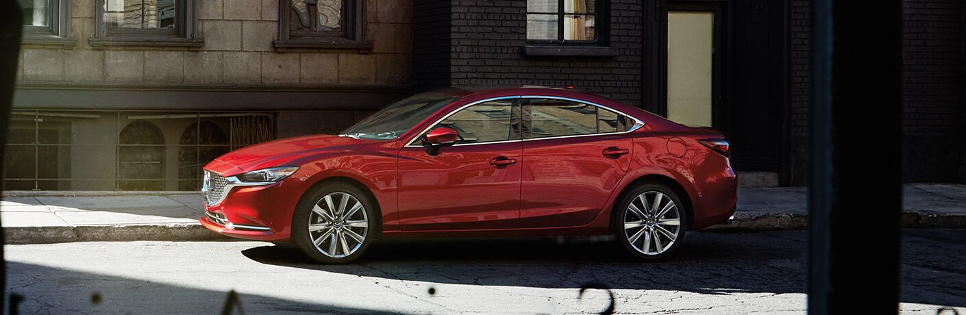 A left profile photo of the 2019 Mazda6 parked in front of a building.