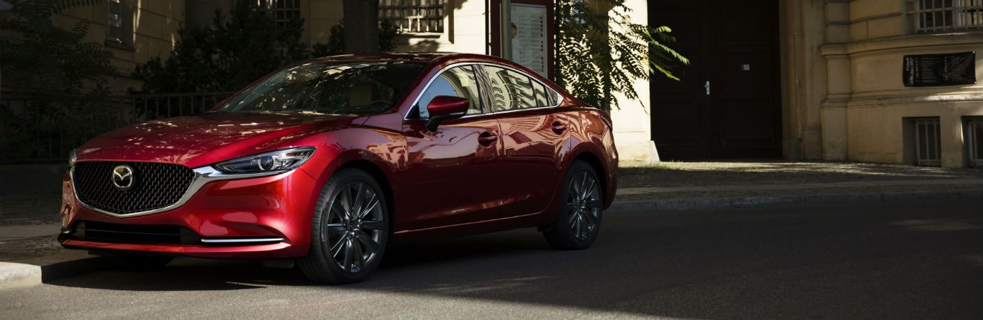 A front left quarter photo of the 2019 Mazda6 parked by a building.