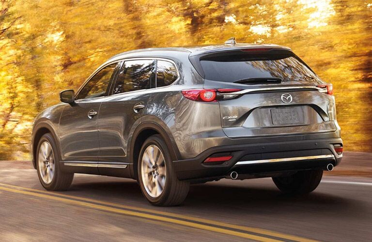 2018 Mazda CX-9 exterior back fascia and drivers side going fast on road with yellow tree leaves