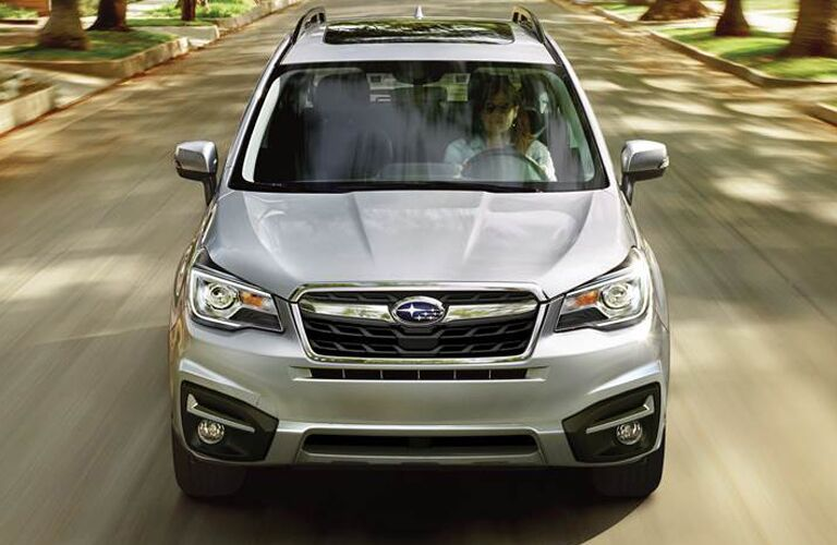 2018 Subaru Forester exterior front fascia and top view with woman driving on town road