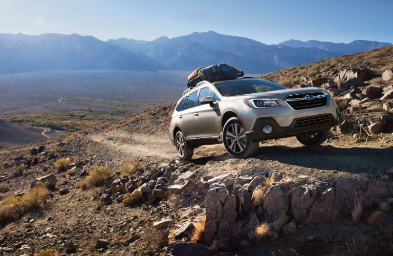 2018 Subaru Outback exterior front fascia and passenger side with cargo on roof and going up rocky dirt road