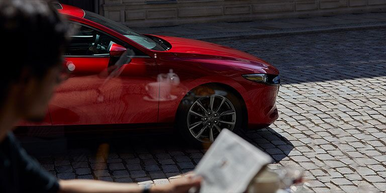 2019 Mazda3 driving in front of a building on a city street