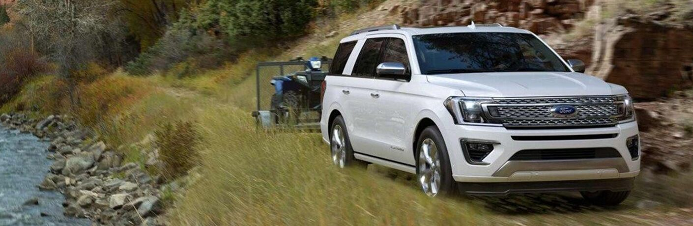 Exterior view of a white 2019 Ford Expedition towing a trailer with a four-wheeler on it