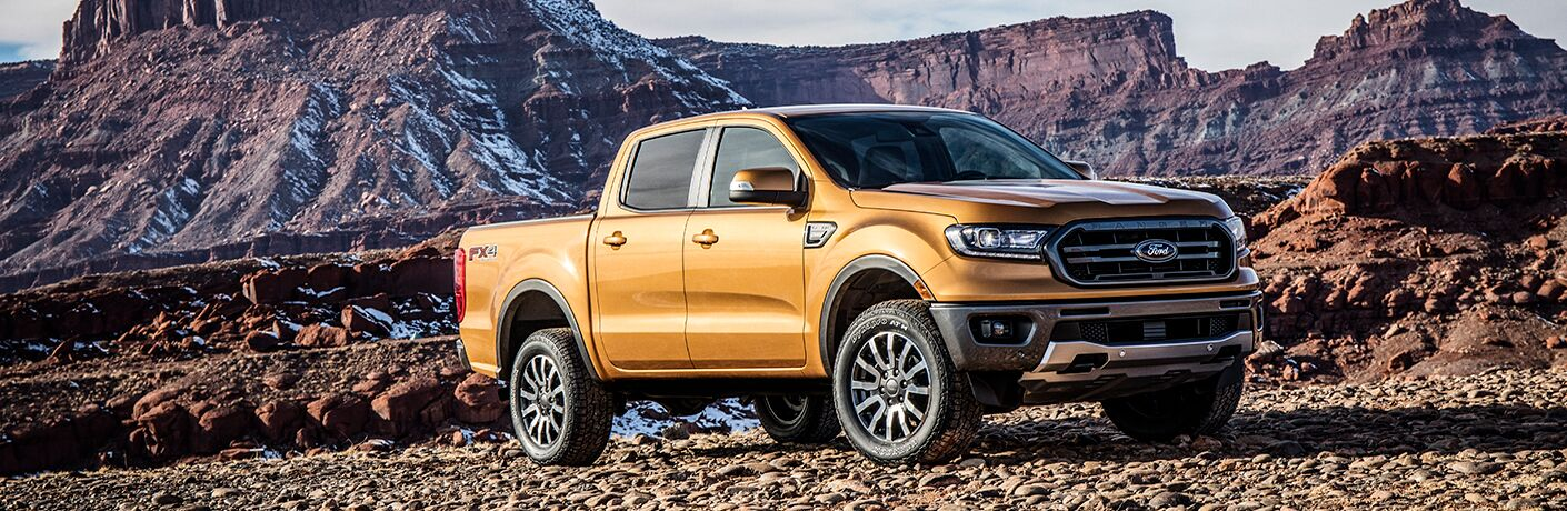 2019 Ford Ranger exterior shot with golden brown paint color parked on a rocky plain near a red ash mountain range