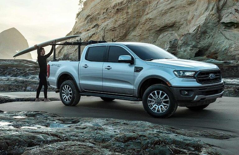 2019 Ford Ranger exterior shot parked on a gray beach next to a rocky cliff as a surfer loads his boards into the truck bed