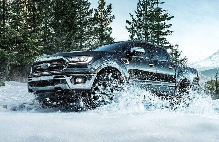 2019 Ford Ranger exterior shot with black paint color climbing hills of snow within an open forest