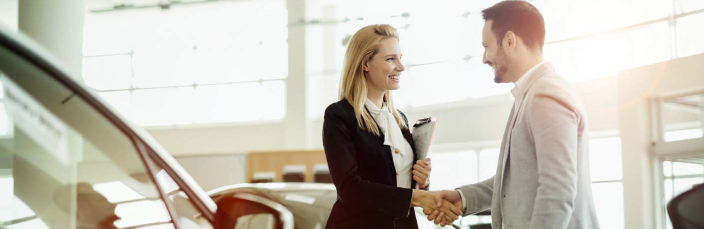 Man and woman shaking hands after transaction in modern dealership