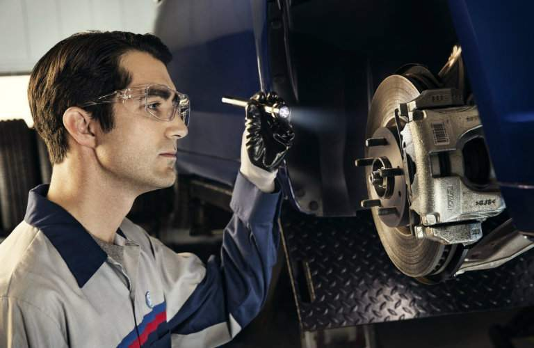 Ford Mechanic using flashlight to inspect vehicle brake system