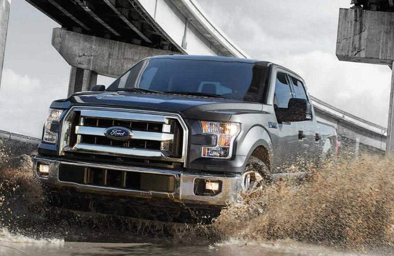 black ford f 150 driving through mud