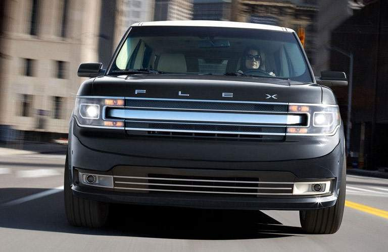 black ford flex on highway, grille view