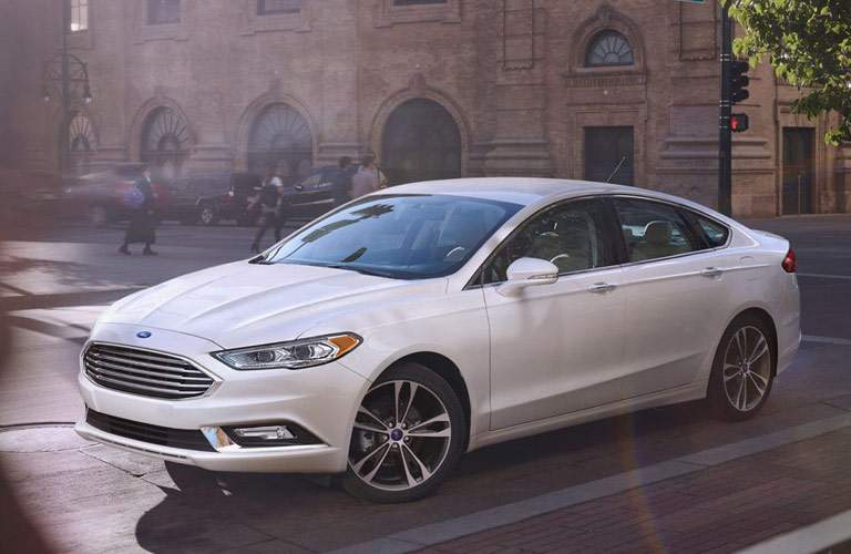 white ford fusion driving in city