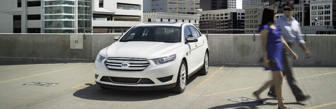 white ford taurus atop parking garage