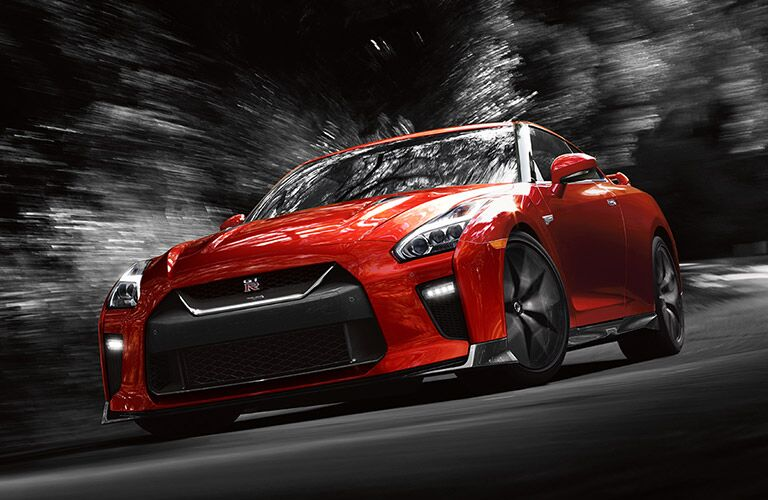 Red 2017 Nissan GT-R drives through a stylized nighttime environment at high speed. Exterior front/side angled view.
