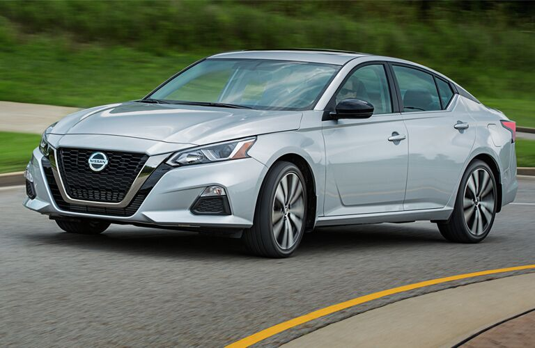 Silver 2019 Nissan Altima drives down a highway.