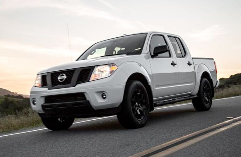 Low-angled view from the front of an off-white 2019 Nissan Frontier driving down a desert highway at dawn.