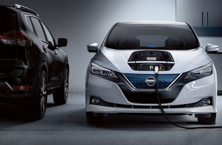 White 2019 Nissan Leaf with a compartment on its hood opened up and a big charging cord plugged in. Head-on view parked in a garage by a cabinet.