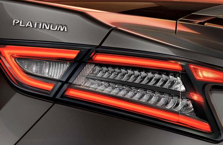 """Close-up taillight view of a 2019 Nissan Maxima. The word """"Platinum"""" is visible above the light."""