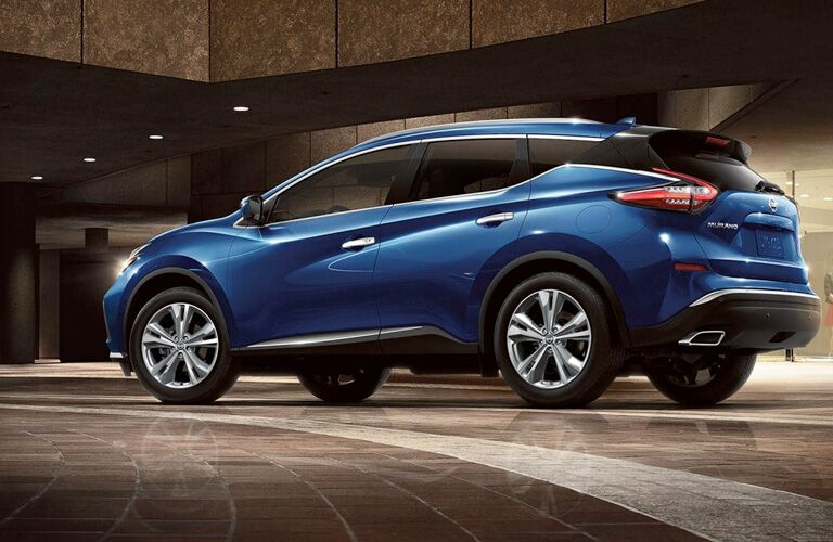 Blue 2019 Nissan Murano side/rear angled view, parked in a nice fancy room.
