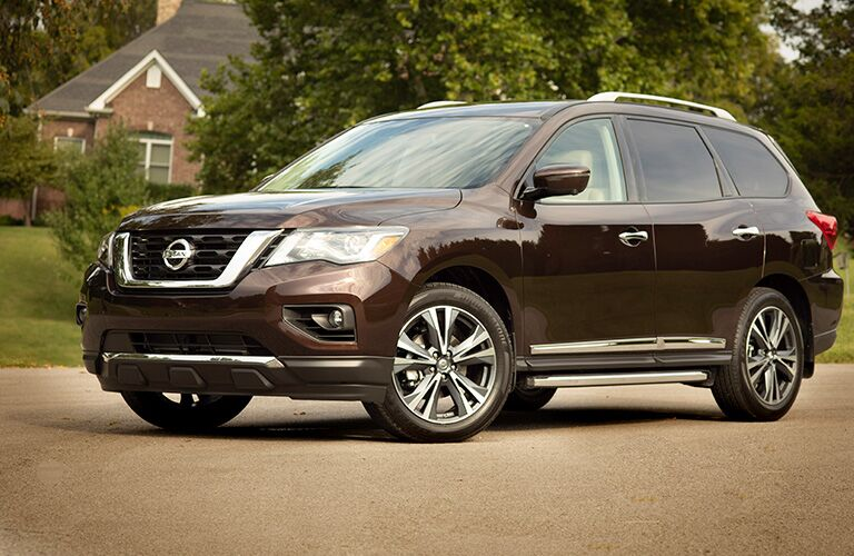 Brown 2019 Nissan Pathfinder exterior side/front angled view, parked on the street in front of a suburban brick homestead.