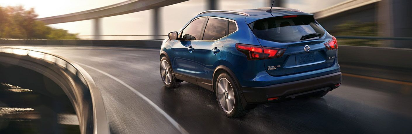 Blue 2019 Nissan Rogue Sport cruises around a highway curve.