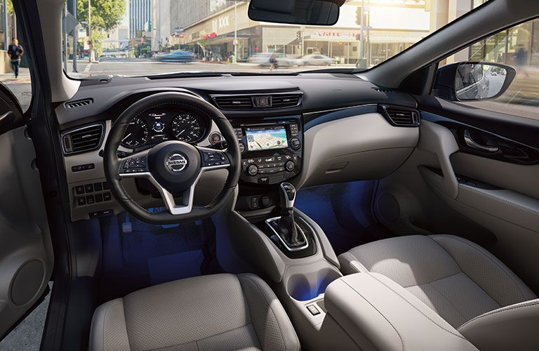 Interior front cabin of a 2019 Nissan Rogue Sport driving through a city.