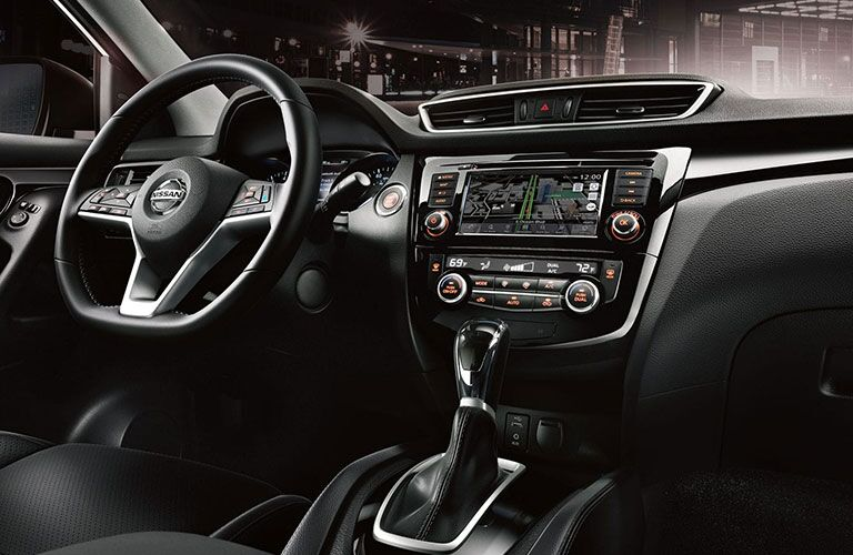 Interior front steering wheel, dash, and shifter of a 2019 Nissan Rogue Sport, in a city at night.