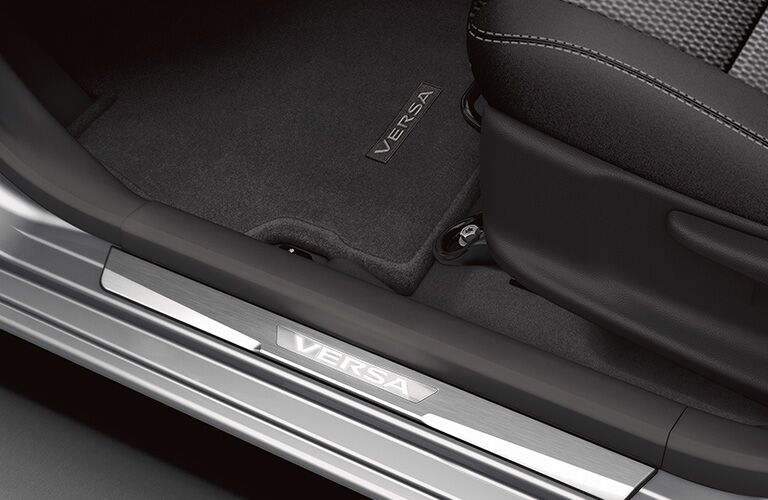 "Interior door frame with ""Versa"" emblem. Floormat with ""Versa"" emblem. Seat and stitching."
