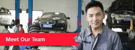 "A man smiles at the camera in an autoshop. White text on a red banner reads, ""Meet Our Team."""