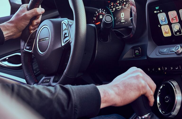 hands gripping the steering wheel and gear shift in a 2018 Chevy Camaro