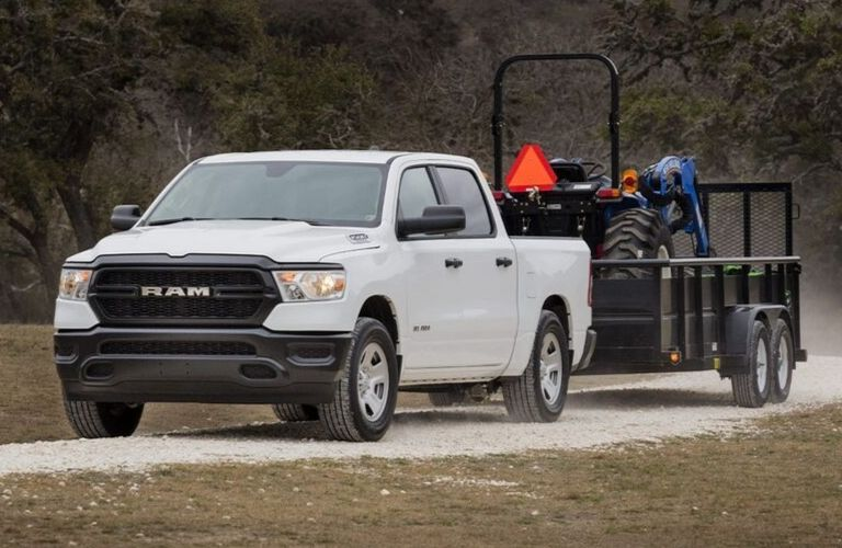 2019 Ram 1500 towing a tractor on a trailer